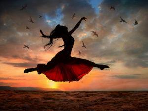 Jumping woman at sunset